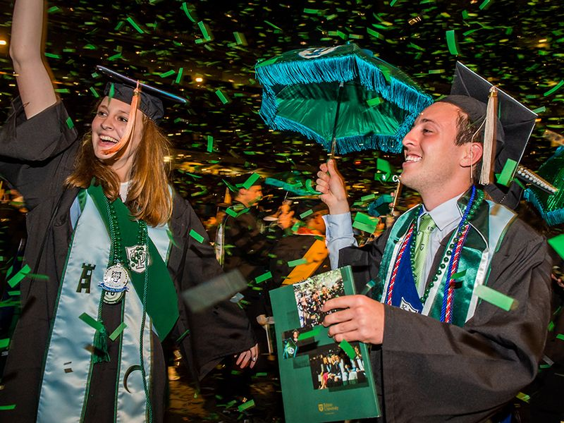 Students celebrate as confetti rains down at the end of the Unified Commencement ceremony